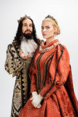 interracial king and queen in medieval clothing and crowns isolated on white