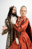 hispanic king in crown and medieval clothing looking at displeased blonde wife isolated on white