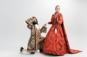 hispanic king in crown and medieval clothing standing on knee while holding hand of blonde queen on white