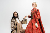 hispanic king in crown and medieval clothing holding hand of blonde queen on white