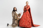 hispanic king in crown and medieval clothing standing on knee while blonde queen showing no gesture on white