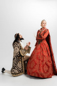 hispanic king in crown and medieval clothing standing on knee while blonde queen in dress showing no gesture on white