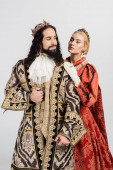 blonde queen in royal crown hugging hispanic king in medieval clothing isolated on white