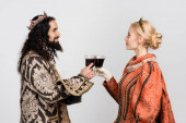 interracial historical couple in medieval clothing and crowns clinking glasses of red wine isolated on white