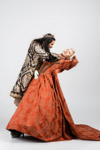 full length of cruel hispanic king in medieval clothing choking blonde queen in golden crown on white