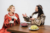 happy interracial historical couple in crowns holding glasses of red wine while sitting at table with grapes isolated on white