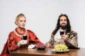interracial historický pár v korunách drží sklenice červeného vína, zatímco sedí u stolu s hrozny izolované na bílém