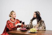 interracial historical couple in crowns clinking glasses of red wine while sitting at table with grapes isolated on white