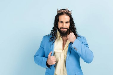 bearded hispanic man in crown adjusting jacket isolated on blue