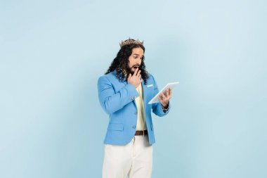 shocked hispanic man in jacket and crown holding digital tablet isolated on blue