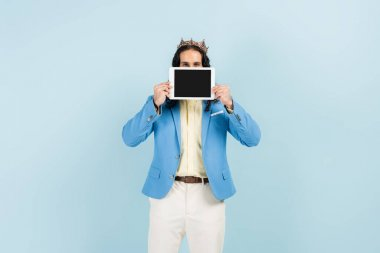 hispanic man in jacket and crown holding digital tablet with blank screen isolated on blue