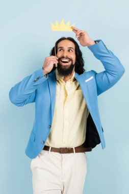 joyful hispanic man in jacket holding paper crown on stick isolated on blue