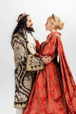 Interracial king and queen in medieval clothing and crowns hugging isolated on white stock vector