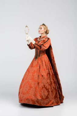 full length of blonde queen in elegant dress and crown looking at mirror on white