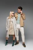 plná délka stylového mladého páru pózujícího na šedé