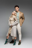 full length of trendy couple posing while standing on grey