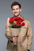 elmosódott mosolygós férfi kezében csokor vörös rózsa elszigetelt szürke