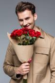 freudiger Mann mit einem Strauß roter Rosen auf grau isoliert