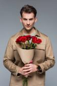 stilvoller Mann mit einem Strauß roter Rosen auf grauem Grund