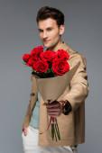 rozmazaný trendy muž drží kytice z červených růží zabalené v papíru izolované na šedé