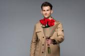 trendiger Mann mit einem Strauß roter Rosen in Papier gewickelt isoliert auf grau