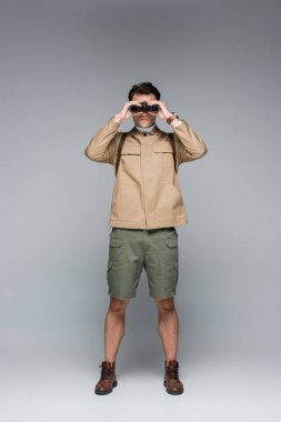 Full length of trendy traveler in shorts and jacket looking through binoculars on grey stock vector