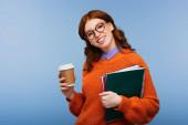 boldog vörös hajú diák szemüvegben és narancssárga pulóverben kezében notebook és papír csésze elszigetelt kék