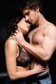 muskulöser Mann umarmt verführerische brünette Frau auf schwarz