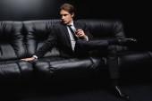 elegantní muž v obleku sedí na koženém gauči se sklenicí whisky na černém pozadí