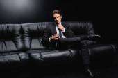 elegantní muž v obleku upravující kravatu a sedí na koženém gauči se sklenicí whisky na černém pozadí