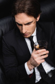 magas látószögű kilátás elegáns férfi öltönyben ül fekete bőr kanapén üveg whiskey