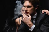Mann im Anzug raucht Zigarette neben Frau auf verschwommenem schwarzem Hintergrund