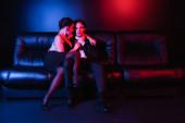 volle Länge der roten und blauen Beleuchtung auf sexy Paar küsst auf schwarzem Ledersofa