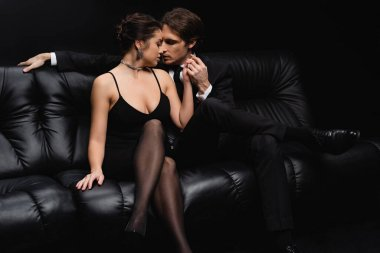 Passionate man in suit kissing seductive woman in slip dress sitting on couch isolated on black stock vector