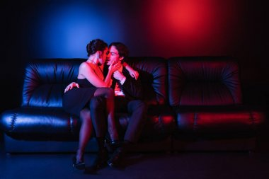 Full length of red and blue lighting on sexy man and woman kissing on black leather sofa stock vector