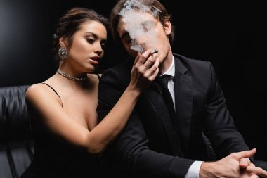 Seductive woman in slip dress holding cigarette near man in suit on black stock vector