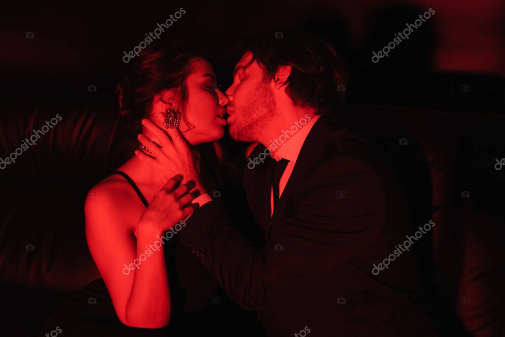 Red lighting on sexy couple kissing on black stock vector