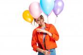 šťastná mladá žena v oranžové košili drží barevné balónky izolované na bílém