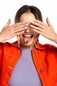 junge Frau bedeckt Augen und streckt Zunge mit Kapsel isoliert auf weiß
