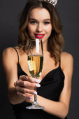 blurred happy woman in black slip dress and tiara holding glass of champagne on grey
