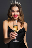 joyful young woman in black slip dress and tiara holding blurred glass of champagne on grey