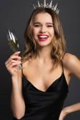 fröhliche Frau in schwarzem Slip-Kleid und Diadem mit einem Glas Champagner auf grau