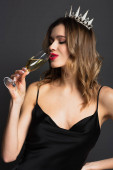 radostná mladá žena v černé kombiné šaty a tiára drží sklo a pití šampaňské na šedé