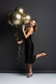 plná délka užaslé mladé ženy v černé kombiné šaty drží zlaté balónky na šedé