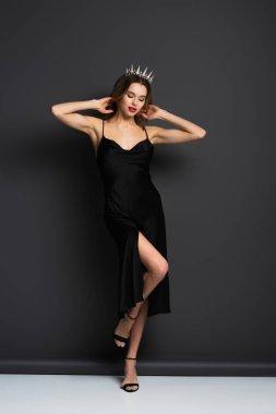 Full length of elegant woman in black slip dress and tiara with diamonds on grey stock vector