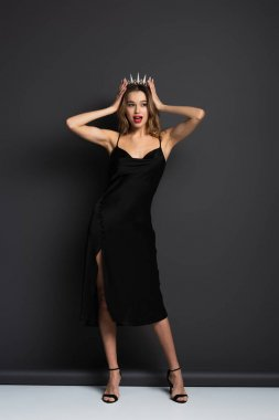 Full length of amazed woman in black slip dress adjusting tiara with diamonds on grey stock vector
