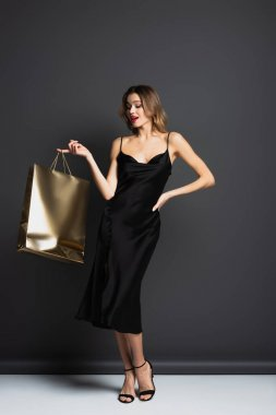 Full length of young woman in black slip dress holding shiny shopping bag while standing with hand on hip on grey stock vector