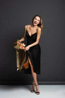 Full length of happy young woman in black slip dress putting gift box in shiny shopping bag on grey stock vector