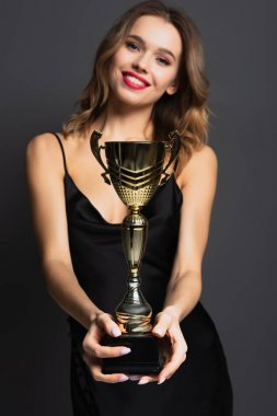 Blurred happy young woman in black slip dress holding golden trophy on grey stock vector