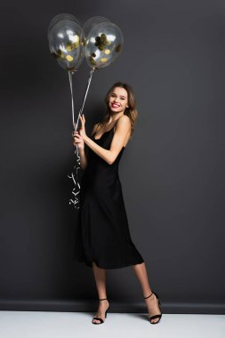 Full length of smiling young woman in black slip dress holding balloons on grey stock vector